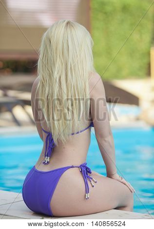 Elegant sexy blonde woman in the purple bikini on the sun-tanned slim and shapely body is posing near the swimming pool.
