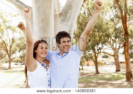 Young couple in the park celebrating