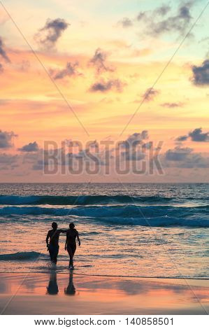 Seascape beautiful sunset beach with silhouette couples walking.