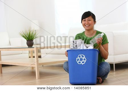 Woman putting plastic bottle into recycle bin