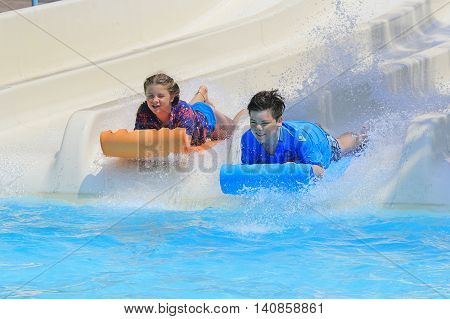 Rhodes Greece-Jun 27 2016:Two young children on the mat racer slide in Water park.Mat racer slide is very popular for young people in the Water Park.Water Park is located on the island of Rhodes in Greece and one of the most largest in Europe