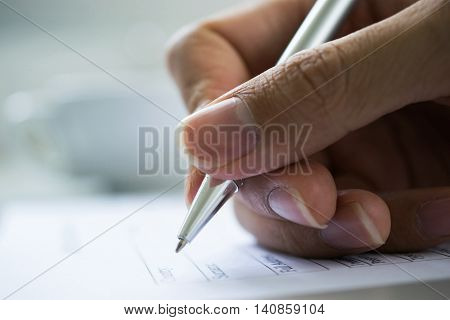 hand with pen over checklist form,Businessman's hand with pen completing personal information on a form