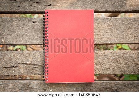 Red cover notebook with blank area on front cover on outdoor rustic wood table in morning time with natural lighting