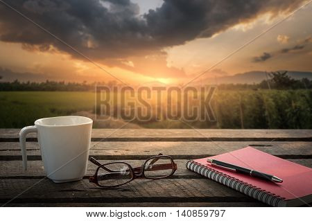 Pen opened notebook glasses and coffee cup on outdoor wood table in morning time on weekend with sunrise landscape view in blurry background. Weekend morning lifestyle concept