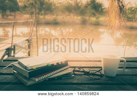 Pen opened notebook glasses and coffee cup on outdoor wood table in morning time on weekend. Freelance business working listyle concept with vintage filter effect
