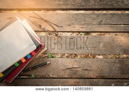 Pen opened notebook glasses and coffee cup on outdoor wood table in morning time on weekend. Freelance business working lifestyle concept