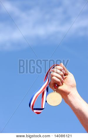 Hand holding gold medal