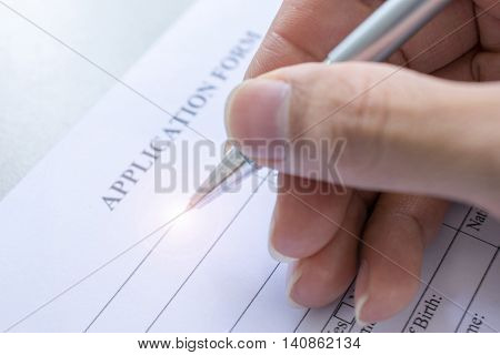 hand with pen over application form completing personal information on a form