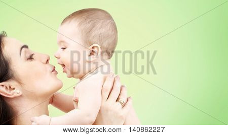 family, motherhood, parenting, people and child care concept - happy mother kissing adorable baby over green background