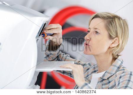 mature blond woman repairing ventilation
