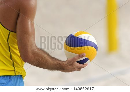 Volleyball player is a male athlete volley ball player getting ready to serve the ball.