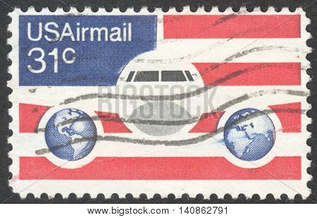 MOSCOW RUSSIA - CIRCA APRIL 2016: a post stamp printed in the USA shows a plane and globes circa 1976