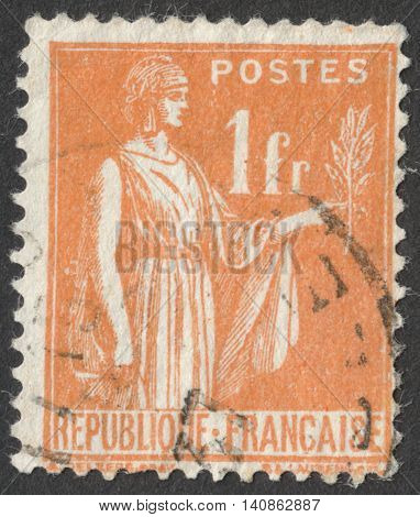 MOSCOW RUSSIA - CIRCA APRIL 2016: a post stamp printed in FRANCE shows a statue of a woman with a branch circa 1932-1933