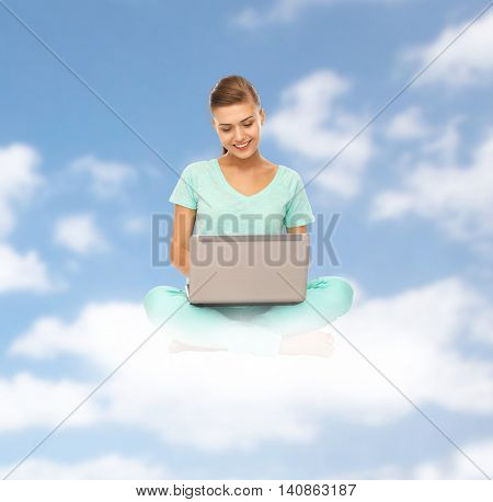 people, computing and technology concept - happy young woman with laptop computer sitting on cloud over blue sky background