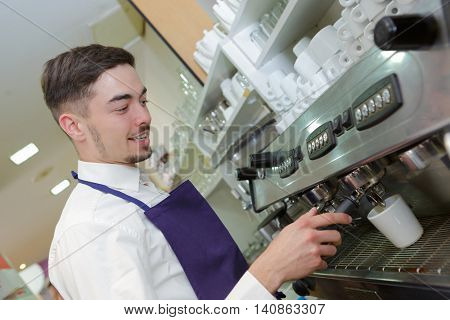 smiling waiter making cup of coffee at the coffee shop