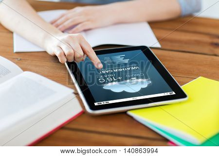 business, education, technology and internet concept - close up of student woman with weather forecast application on tablet pc computer and notebook at home