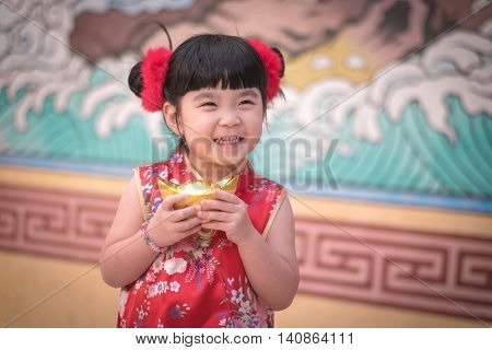 China Girl In Traditional Chinese Dress Greeting, Holding A Gold Ingot Standing