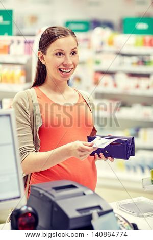 medicine, pharmaceutics, health care and people concept - happy pregnant woman with wallet in at cash register drugstore