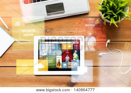 education, business, mass media and technology concept - close up of tablet pc computer, laptop and earphones on wooden table with internet application on screen