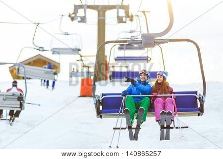 Smiling couple in sportswear on a lift