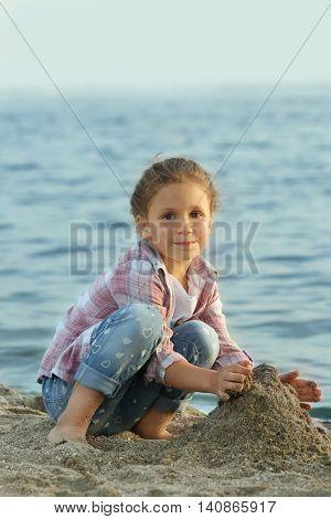 Cute girl building sand tower on beach