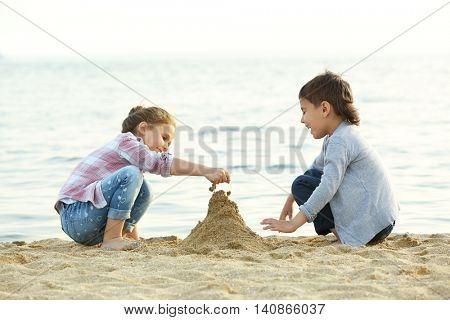 Two cute kids building a sand tower