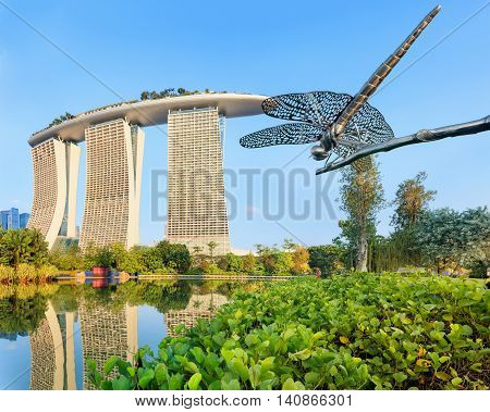 Singapore, Republic of Singapore - May 5, 2016: Gardens by the Bay, Marina Bay Sands hotel and Dragonfly scultpure reflecting in lake at sunrise