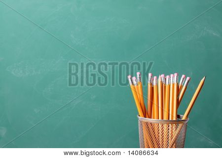 Lápices con fondo de pizarra para el espacio de la copia
