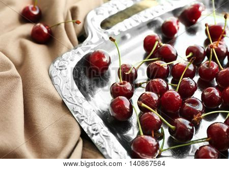 Fresh ripe cherries on metal tray, closeup