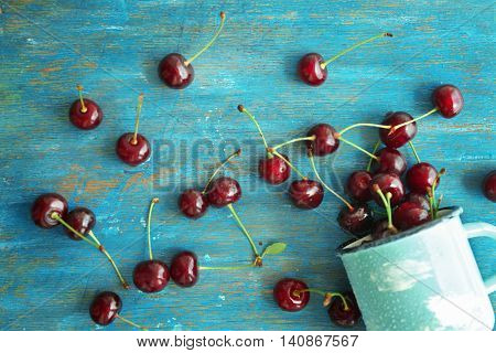 Fresh ripe cherries on blue wooden background