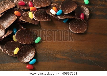 Chocolate crisps and candies on wooden background