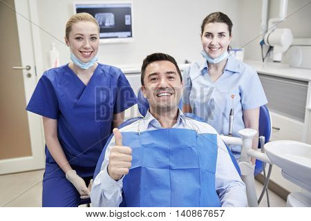 people, medicine, stomatology, gesture and health care concept - happy female dentist with assistant and man patient showing thumbs up at dental clinic office