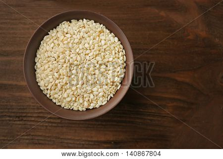 Bowl with white sesame on wooden background