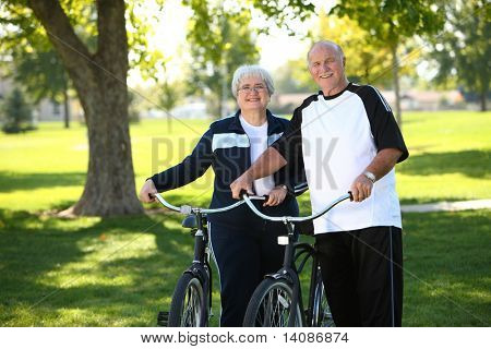 Senior couple at park with bikes