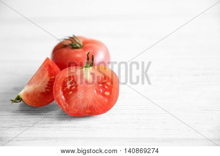 Red juicy tomato and slices on light wooden background