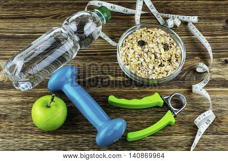 The concept of a healthy lifestyle. Apple dumbbell water expander hand and measuring tape on rustic wooden table.
