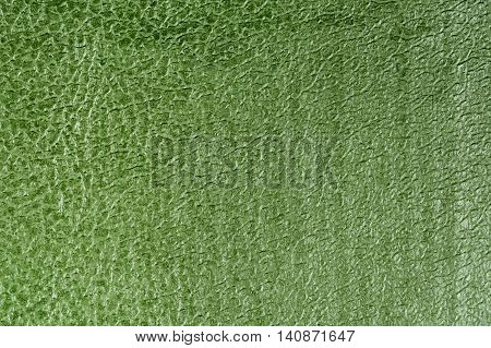 Green embossed decorative leatherette texture background, close up