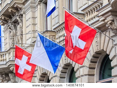 Zurich, Switzerland - 30 July, 2016: facade of the Credit Suisse building on Paradeplatz square decorated with flags of Switzerland and Zurich. Credit Suisse Group is a Swiss multinational financial services holding company headquartered in Zurich.