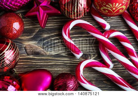 Christmas balls and Christmas Candy Cane on wooden background.