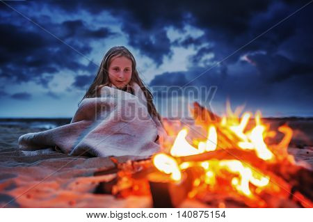 A young girl on the beach at night wrapped in a blanket is heated by the fire.