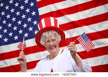 Patriotic senior woman waving flags and smiling