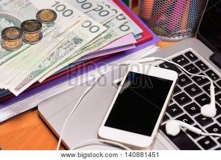 Workplace with money and electronic devices - cellphone, headphones for music and laptop computer. Mobile phone and Polish money banknotes on keyboard of notebook. Concept of payment and savings.