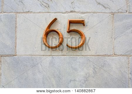 Marble wall with address numbers of 65 made of bronze