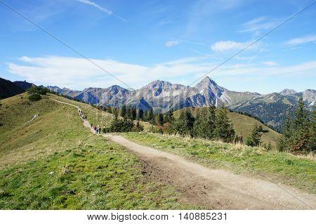Hike on the Saalfeld High Mountain Trail in Tyrol, Austria,  sunny autumn day, peaks of the Tannheim Mountains, mountain meadows, a mountain trail and hikers,