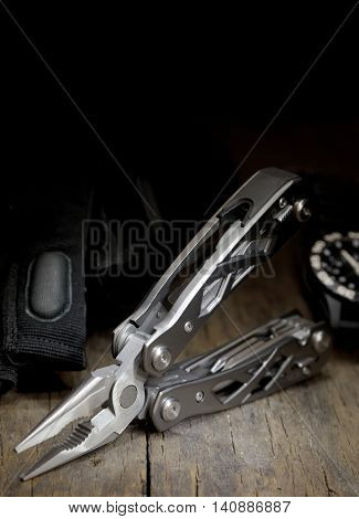 stainless steel multitool isolated on wooden table