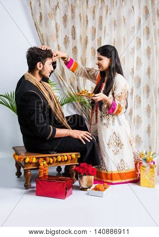 indian sister applying tika on brother's forehead, enjoying and celebrating Raksha Bandhan festival poster