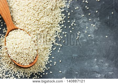 Sesame seeds in wooden spoon on dark gray stone background top view blank space for text