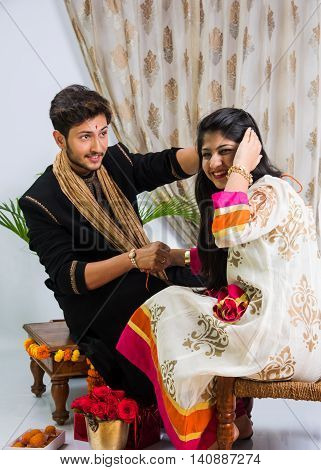 Indian young sister tying rakhi on brother's wrist, a tradition on Raksha Bandhan festival