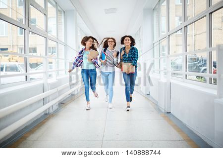 Happy girls running along the corridor after classes