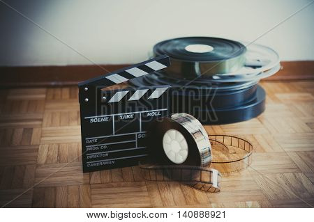 35 mm cinema movie clapper board and film reels in background on wooden floor pastel colors